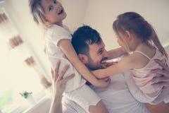 Gelukkige vader en kleine dochters die tijd thuis doorbrengen Stock Afbeelding