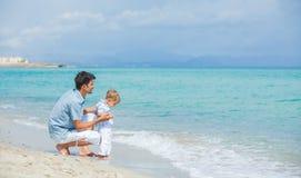 Gelukkige vader en zijn zoon die bij strand spelen stock foto's