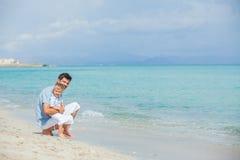 Gelukkige vader en zijn zoon die bij strand spelen royalty-vrije stock foto's