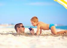 Gelukkige vader en zoon die op slimme telefoon, op het strand samen spreken Royalty-vrije Stock Fotografie