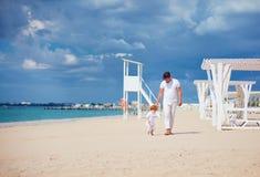 Gelukkige vader en zoon die op zandig strand, de zomervakantie lopen Stock Foto's