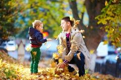 Gelukkige vader en zoon die pret in de herfstpark hebben Royalty-vrije Stock Afbeeldingen