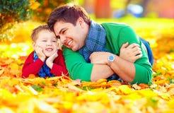 Gelukkige vader en zoon die pret in de herfstpark hebben Stock Afbeeldingen