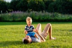 Gelukkige vader en zoon die pret openlucht op weide hebben Royalty-vrije Stock Foto's