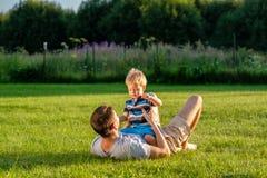Gelukkige vader en zoon die pret openlucht op weide hebben Royalty-vrije Stock Foto