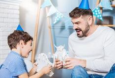 Gelukkige vader en zoon die stuk speelgoed robot van strijden genieten Royalty-vrije Stock Foto's