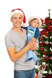 Gelukkige vader en zoon met santahoeden Stock Foto's