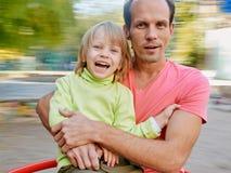 Gelukkige Vader en zoon op carrousel Royalty-vrije Stock Foto