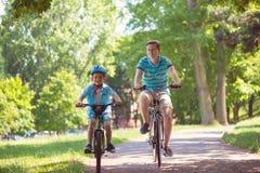 Gelukkige vader en zoonsrit op fietsen Royalty-vrije Stock Foto's
