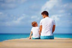 gelukkige vader en zoonszitting bij pijler en de bespreking stock afbeeldingen
