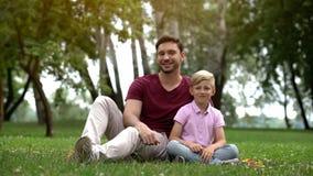 Gelukkige vader en zoonszitting in park, advertentie van sociale steun voor enige vaders royalty-vrije stock foto's