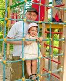 Vader met dochter bij het spelen van gebied Stock Foto's