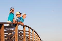 Gelukkige vader met zijn zonen die zich op houten brug bevinden Stock Foto