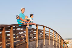 Gelukkige vader met zijn zonen en weinig dochter die zich op houten brug bevinden Stock Foto