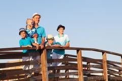 Gelukkige vader met zijn zonen en weinig dochter die zich op houten brug bevinden Royalty-vrije Stock Foto's