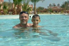 Gelukkige vader met zoon in pool Stock Foto
