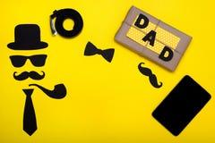 Gelukkige Vader` s dag E De hoed, de glazen, de snor, de rokende pijp, de riem, de tablet, en de vlinderdas, op een gele pa Royalty-vrije Stock Foto