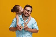Gelukkige vader` s dag! leuke papa en dochter die op gele rug koesteren Stock Foto