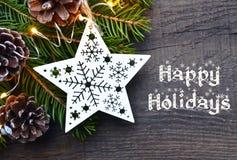 Gelukkige Vakantie De Kerstmisdecoratie met spar, de slingerlichten en witte houten Kerstmis spelen op oude houten achtergrond me Royalty-vrije Stock Foto