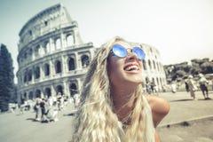 Gelukkige vakantie in Rome, glimlachend jong blonde voor colosseum in Rome in Italië stock fotografie
