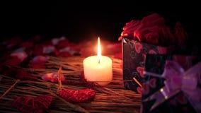 Gelukkige Valentine-dag met lengte van giftdozen, kaars het branden en bloembloemblaadjes stock videobeelden