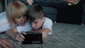 Gelukkige van de van de familiemamma, papa en zoon het letten op films en speelspelen op telefoons en laptops stock footage