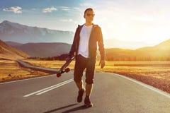 Gelukkige van de de gang longboard zonsondergang van de mensenschaatser de bergweg royalty-vrije stock fotografie