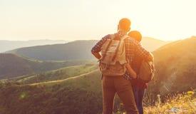Gelukkige van de paarman en vrouw toerist boven berg bij zonsondergang stock afbeeldingen