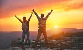 Gelukkige van de paarman en vrouw toerist boven berg bij zonsondergang stock foto's
