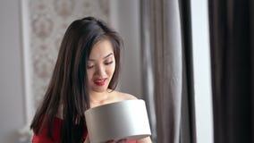 Gelukkige verbaasde elegante Aziatische vrouw het openen giftdoos en thuis het glimlachen van comfortabel binnenland