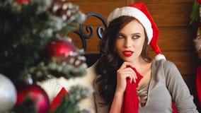 Gelukkige Verbaasde Vrouw in Santa Hat en Glimlachen Mooi Brunette met Lang Donker Haar en Santa Clause Cap Next aan Kerstmisboom stock footage