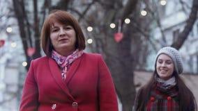 Gelukkige vergadering van rijpe vrouw en haar gegroeide dochter in het park Lichten op achtergrond stock videobeelden