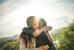Gelukkige vergadering van twee vrienden die bij zonsondergang koesteren openlucht - Prettig ogenblik die van jonge zusters in de  stock afbeeldingen