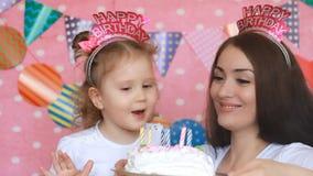 Gelukkige Verjaardag De moeder en de Dochter blazen uit kaarsen op cake bij partij en maken een wens Het mamma wenst geluk, omhel stock video