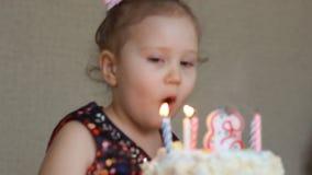 Gelukkige Verjaardag Het leuke kind maakt een wens en slagen kaarsen op cake bij partij op Grappig meisje op de partij stock videobeelden