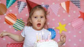Gelukkige Verjaardag Het leuke kind maakt een wens en slagen kaarsen op cake bij partij op Grappig meisje en een vakantie Roze stock video