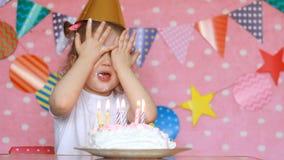 Gelukkige Verjaardag Het leuke kindmeisje maakt een wens en slagenkaarsen op en eet cake bij partij stock videobeelden