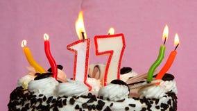 Gelukkige verjaardag 17 met cake en kaarsen op roze achtergrond stock videobeelden