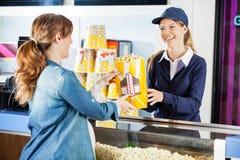Gelukkige Verkoper die Popcorn geeft aan Zwangere Vrouw bij royalty-vrije stock foto's