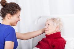 Gelukkige verpleegster die een bejaarde helpen Royalty-vrije Stock Afbeeldingen