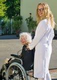 Gelukkige Verpleegster en Bejaarde Patiënt buiten het Ziekenhuis stock foto