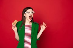 Gelukkige verraste donkerbruine dame met creditcard stock afbeelding