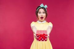Gelukkige verraste jonge vrouw die u een giftdoos geven royalty-vrije stock foto's