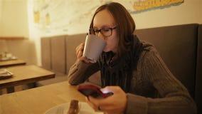 Gelukkige, verraste vrouw die smartphonezitting in koffie gebruiken Jong Kaukasisch meisje die in glazen sms en het drinken koffi stock video