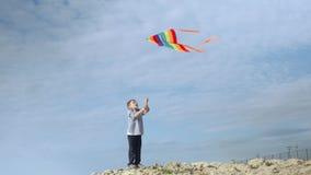 Gelukkige verrukkelijk weinig jongen met gekleurde vlieger door het overzees stock footage