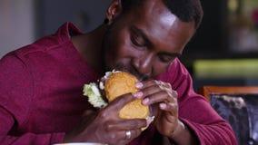 Gelukkige vette Afrikaanse Amerikaanse mens die een hamburger eten stock video