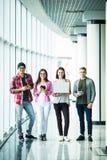 Gelukkige vier vrienden die en moderne gadgets zich binnen bevinden gebruiken Stock Foto's