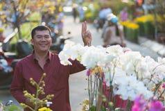 Gelukkige Vietnamese mens het kopen orchideeën royalty-vrije stock fotografie