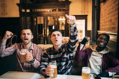 Gelukkige voetbalventilators of mannelijke vrienden die bier drinken en overwinning van beste team of nationaal team vieren bij b royalty-vrije stock fotografie