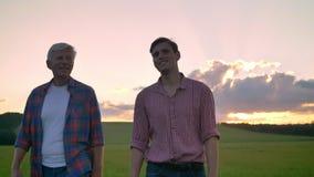Gelukkige volwassen zoon met zijn vader die op tarwegebied lopen en, mooie hemel met binnen wolken tijdens zonsondergang glimlach stock videobeelden